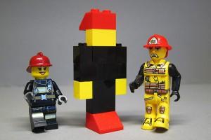 Några historiska LEGO-brandmän. Äldst i mitten  set nr 305, Fire Engine, från 1964 (reproduktion), till höger 4 Juniors set nr 4601, Fire Cruiser, från 2001 och till vänster City set nr 60003, Fire Emergency, från 2013.